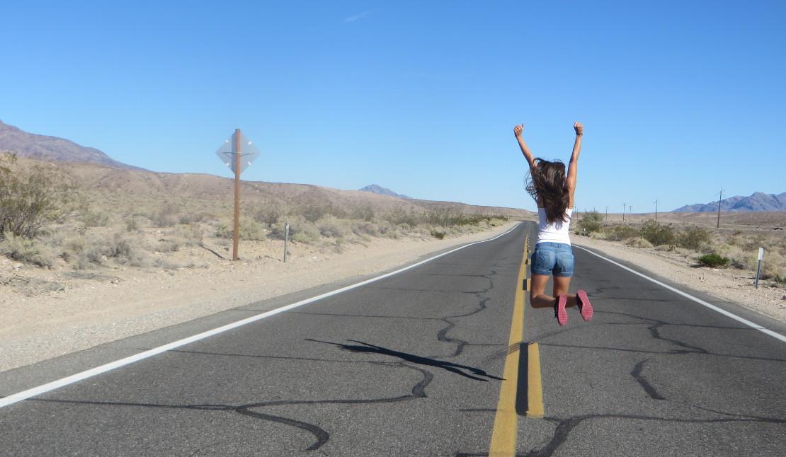 Mädchen auf Roadtrip springt in die Freiheit